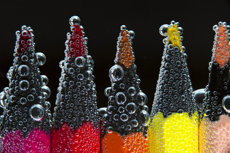 peachy: Colorful pencils in soda water, closeup.