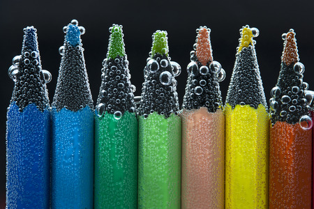 peachy: Bright colorful pencils in soda water. Back to school concept.