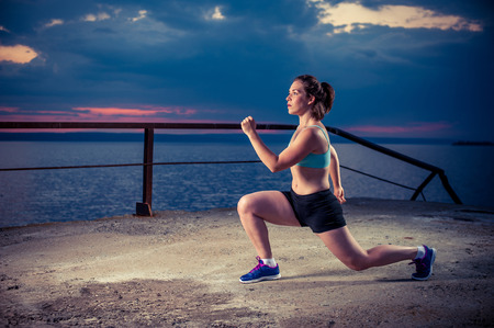 lunges: Young woman in sportswear doing lunges on sea pier. Fitness workout outdoors