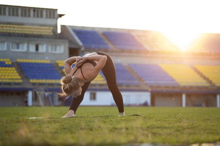 intense: Fit blonde woman in sportswear doing yoga. Intense Side Stretch Pose. Stock Photo
