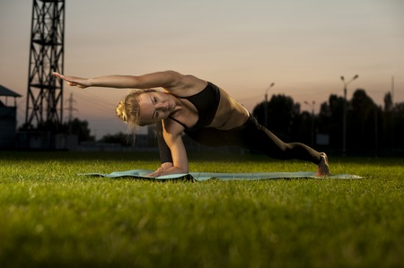 revolved: Blonde woman exercising yoga on green grass outdoors. Revolved Lunge Pose.