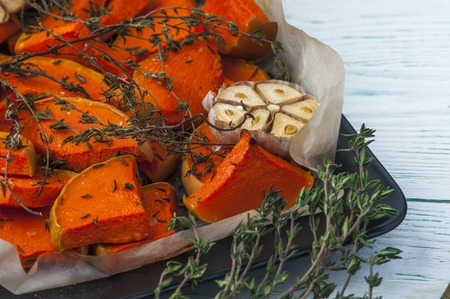 Baked pumpkin with thyme, olive oil and garlic on baking tray. Horizontal view. Vegetarian food. Focus on pumpkin pieces.