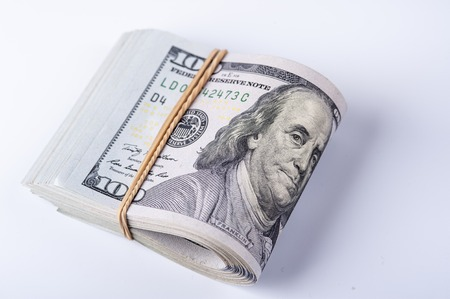 Stack of one hundred dollar bills with rubberband on white background