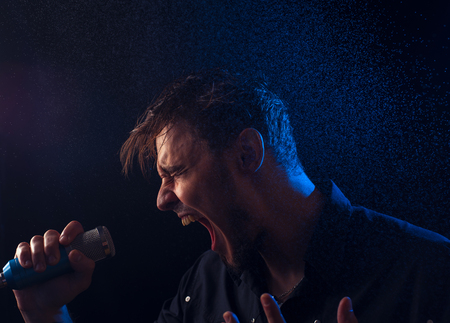 bawl: Male expressive singer on the stage with microphone in his hands Stock Photo