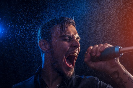 bawl: Young expressive performer singing on microphone on the stage on the background of spotlight and water drops.