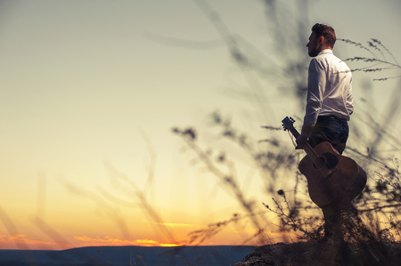 Portrait of young attracive man in casual cloth holding guitar and standing on the mountain at sunset Stock Photo