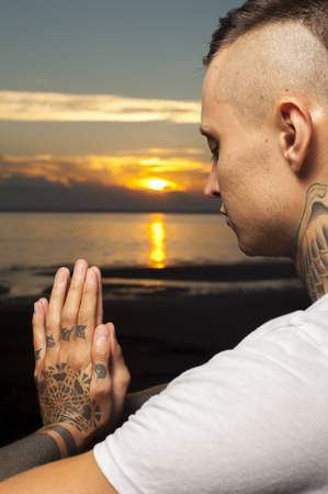 Cropped shot of young tattoo man doing yoga on the beach at sunset cropped shot of young tattoo man doing yoga on the beach at sunset meditation pose thecheapjerseys Choice Image
