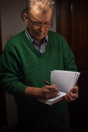 memoir: Portrait of senior man in casual outfit writing on diary.
