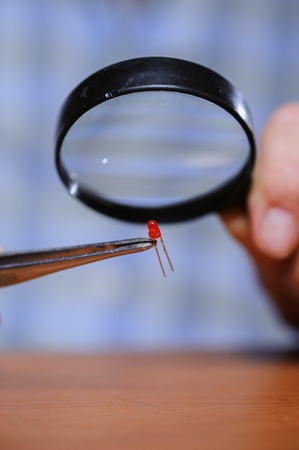 electronical: Closeup of diode and magnifier in male hands. Electronical components.