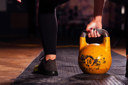 Cropped shot of female athlete exercising with kettlebell. Young sporty woman doing workout in gym.