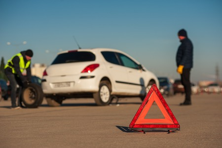 Car assistance technician changing the wheel after car accident. Red triangle warning sign foreground.