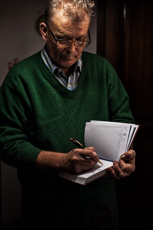 memoir: Senior man in casual outfit and glasses writing on a diary