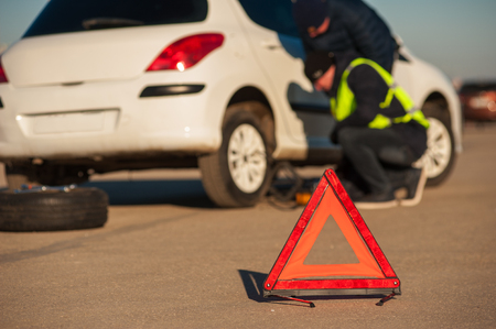 Car assistance technician and male driver changing flat tire. Auto breakdown. Red emergency warning sign. Stock Photo