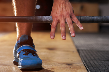 Closeup of male hand holding barbell before training. Power lifting, weightlifting, cross fit equipment. Sports, fitness concept.