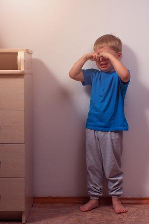 punishment: Crying boy staying in corner for punishment. Child abuse. Stock Photo