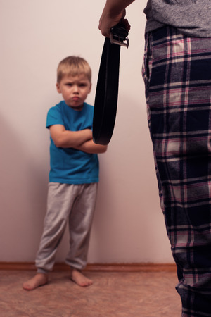 argues: Angry boy and abusive mother with belt. Child abuse. Domestic violence, aggression in the family. Stock Photo