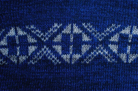 White knitted ornament on blue woolen fabric ftexture. Abstract background, closeup