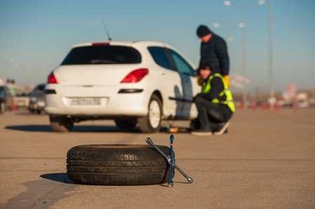 emergency vest: Wheel wrench and tyre on the background of car assistance technician and male driver. Fall or winter sunny day.