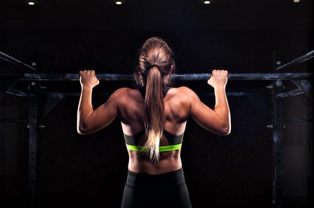 La forte ragazza di misura nel fare degli abiti sportivi tira su sulla barra orizzontale. allenamento fitness in palestra.