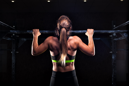 Strong fit girl in sportswear doing pull up exercise on horizontal bar. fitness workout in gym.