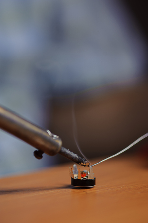 Soldering iron and chip with wire on table, closeup Stock Photo