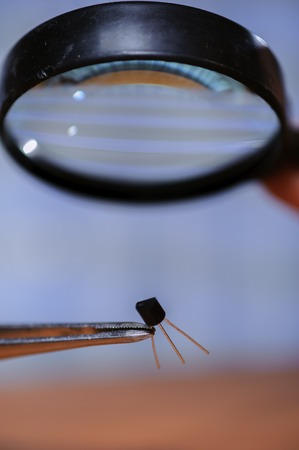 electronical: Diode and magnifier, closeup. Electronical equipment in human hands.