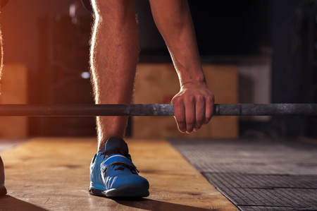 Closeup of male hand holding barbell. Man preparing for dead lift exercise with barbell in gym. Weightlifting, power lifting, cross fit equipment. Sports, fitness concept.