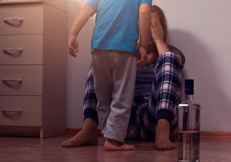 madre borracho sentado en el suelo y cubriendo su rostro de su pequeño hijo asustado. El abuso infantil, la adicción alcohólica. Vidrio y botella, la profundidad de campo.