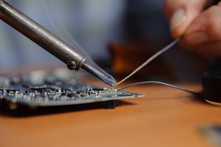 Soldering computer board. Closeup of soldering iron and wire. Stock Photo