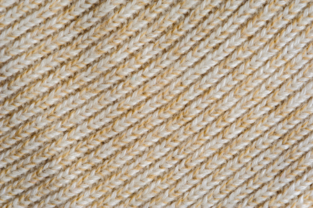 tejido de lana: Closeup of beige knitted woolen fabric texture for wallpaper or an abstract background.