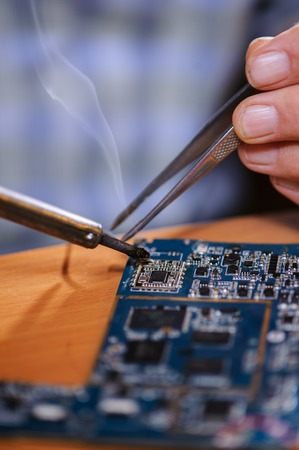 Closeup of male hands with soldering iron and tweezers. Electrician repairing computer board. Stock Photo