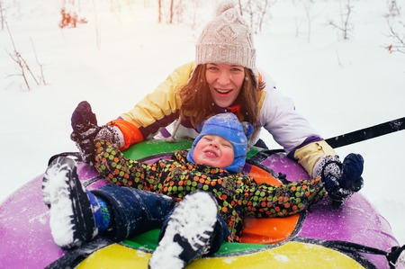 Happy smiling mother and child sit on snow tube