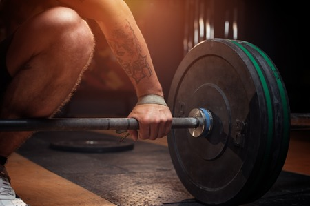 Young man preparing for barbell training in gym Stock Photo