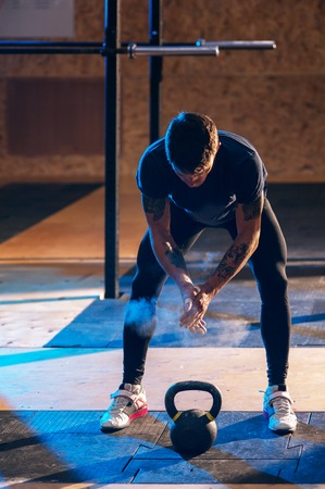 Muscular man exercising with kettle bell in gym Standard-Bild