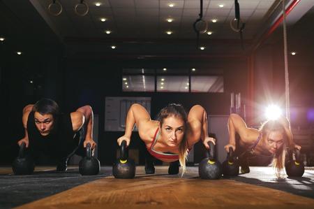 Muscular athletes doing push ups with kettlebell Standard-Bild