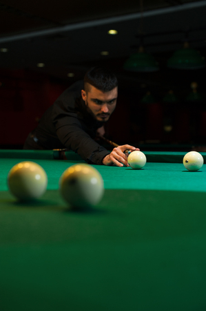 snooker hall: Young handsome man playing billiard game alone Stock Photo