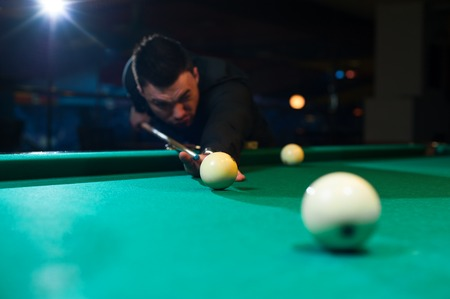 snooker halls: Cropped shot of male adult playing billiard game.