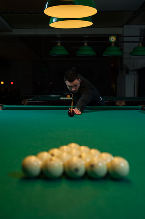 Concentrated man aiming the billiard ball