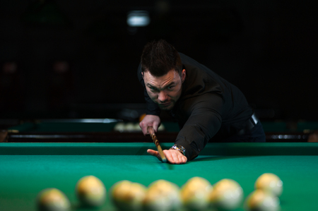 snooker hall: Male adult playing billiard game in club