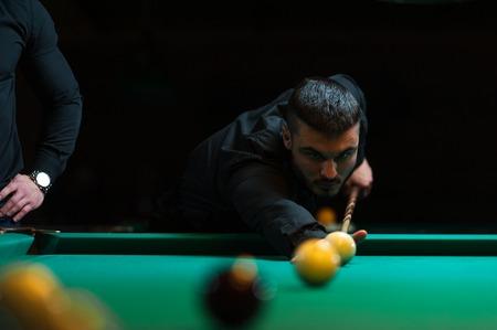 snooker hall: Young man playing billiard in dark club.