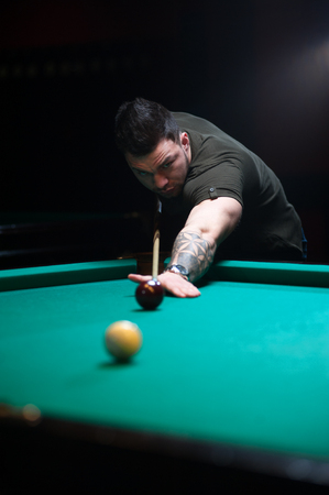 snooker halls: Concentrated man aiming the billiard ball.