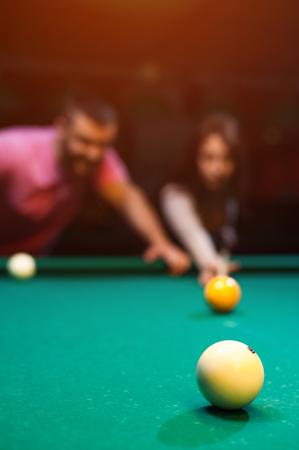 ロマンチックなカップルは暗いクラブでビリヤードをプレイ