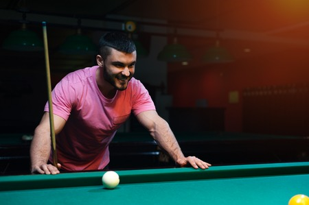 snooker hall: Happy smiling young man playing billiard game