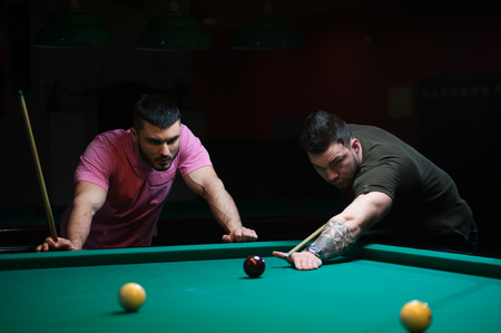 Two male friends playing billiard in dark club Stock Photo