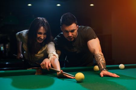 snooker hall: Smiling romantic couple playing snooker in club