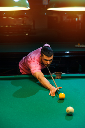 snooker halls: Young caucasian man playing billiard in club.