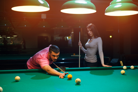 snooker halls: Young romantic couple playing billiard game