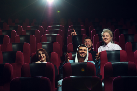 Happy smiling friends watching film in theater