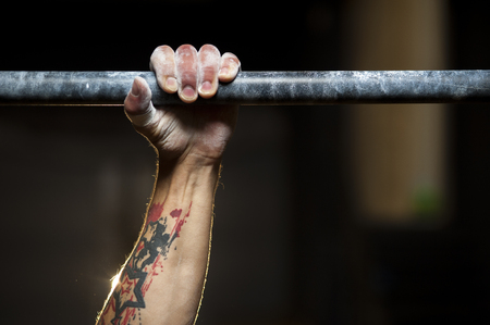Pull ups exercise: male hand in horizontal bar