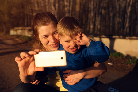 Happy smiling family making selfie at sunset